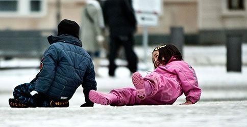 Kinder rutschen auf Glatteis aus