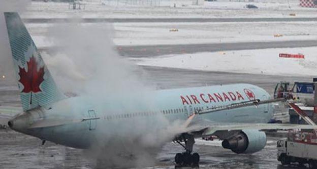 Mitarbeiter des Frankfurter Flughafens enteisen am Montag (21.01.13) auf dem Flughafen in Frankfurt am Main ein Flugzeug der kanadischen Fluglinie Air Canada.
