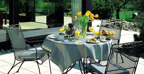 Ein gedeckter Kaffeetisch steht auf einer gefliesten Terrasse